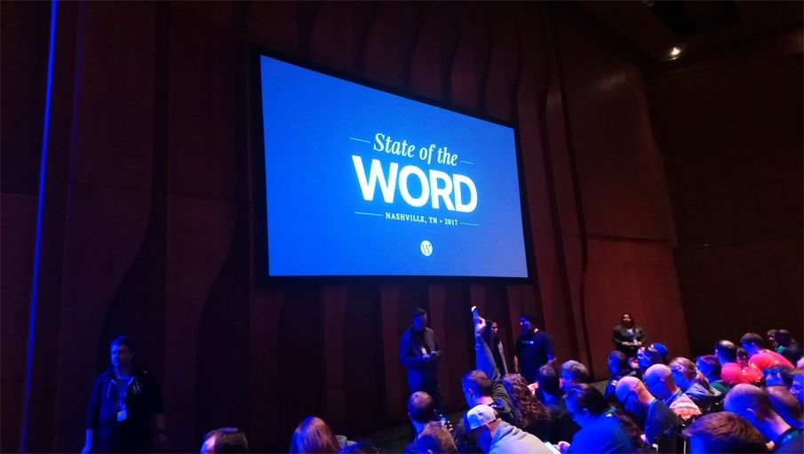 "Projector screen with ""State of the Word"" on the screen in a large conference hall before the presentation"