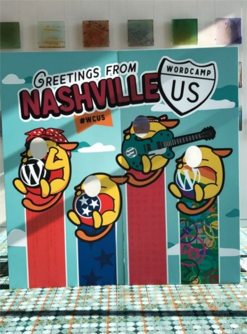 "A board with face holes featuring the Wapuus of WordPress - Caption reads ""Greetings from Nashville #WCUS"""